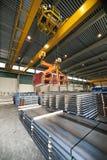 Handling Steel. Huge overhead crane, handling pallets containing steel sheet at a warehouse stock photo