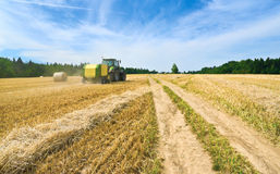 Handling of straw by baler in a field Royalty Free Stock Image