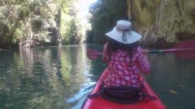 Handlingkamera pov av kvinnan som kayaking i den härliga flickan för bakre sikt för lagunbaksida som paddlar på kajakfartyget arkivfilmer