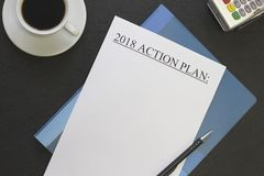 handlingsplan 2018 på en blå mapp med en kaffekopp och en kreditkortmaskin Royaltyfria Foton
