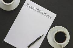 handlingsplanpapper 2018 med koppar för vitt kaffe och en svart penna Arkivbild