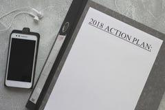 handlingsplanpapper 2018 på en grå kontorsmapp, en mobiltelefon Royaltyfri Fotografi