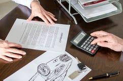 Handlowiec kalkuluje samochodową cenę Fotografia Royalty Free