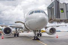 Handlowy pasażerski samolot w parking przy lotniskiem z nosem przednim i gangway - frontowy widok obrazy royalty free