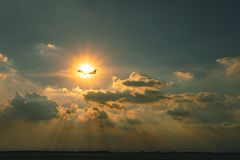 Handlowy samolot lata nad niebem przeciw pięknemu słońce promienia throu obrazy stock