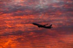 Handlowy samolotowy latanie nad dramatyczne chmury podczas zmierzchu zdjęcie royalty free