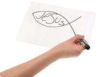 Handmädchen, das ein christliches Fischsymbol zeichnet Stockfotografie