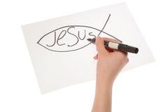Handmädchen, das ein christliches Fischsymbol zeichnet Stockbilder