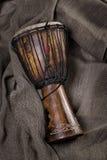 Африканская рука барабанчика djembe высекла лежать на ткани холстины Стоковые Фотографии RF
