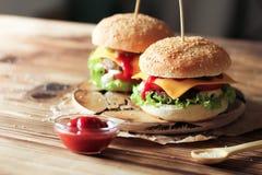 2 handmade бургера с говядиной, салатом и сыром на деревянном столе Стоковая Фотография