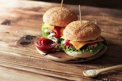 2 handmade бургера с говядиной, салатом и сыром на деревянном столе Стоковое Изображение RF