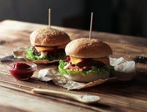 2 handmade бургера с говядиной, салатом и сыром на деревянном столе Стоковые Фотографии RF