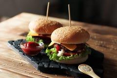 2 handmade бургера с говядиной, салатом и сыром на деревянном столе Стоковое Изображение