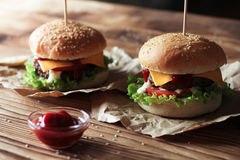 2 handmade бургера с говядиной, салатом и сыром на деревянном столе Стоковые Изображения