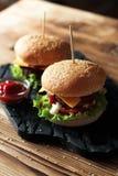 2 handmade бургера с говядиной, салатом и сыром на деревянном столе Стоковая Фотография RF