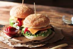 2 handmade бургера с говядиной, салатом и сыром на деревянном столе Стоковое Фото