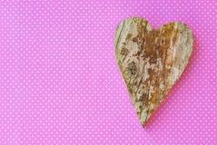 Handmade деревянное сердце на пинке поставило точки предпосылка для поздравительной открытки влюбленности Стоковая Фотография