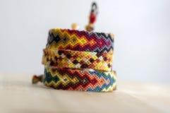 3 handmade домодельных красочных естественных сплетенных браслета приятельства изолированного на деревянной предпосылке стоковая фотография