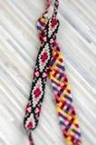 2 handmade домодельных красочных естественных сплетенных браслета приятельства изолированного на светлой деревянной предпосылке стоковая фотография rf