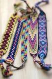 5 handmade домодельных красочных естественных сплетенных браслетов приятельства на деревянной доске, группе в составе аксессуары  стоковое изображение