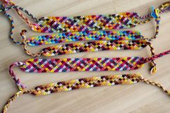 5 handmade домодельных красочных естественных сплетенных браслетов приятельства на деревянной доске, checkered картине стоковые фото