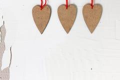 3 handmade деревянных сердца на старой стене гипсолита стоковые фото