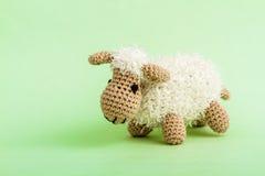 Handmade игрушка овечки вязания крючком на зеленой предпосылке Стоковые Изображения RF