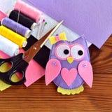 Handmade игрушка сыча войлока, войлок покрывает, ножницы, поток, штыри, игла на коричневой деревянной предпосылке предпосылка зас Стоковые Фотографии RF