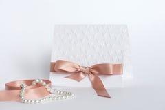 Handmade карточка с выбитыми сердцами и бежевый смычок на белой предпосылке Стоковое Фото