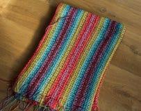 Handmade красочное связанное одеяло шерстей на деревянной предпосылке стоковые изображения