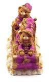 Handmade медведи рождества в санях в куртки и шляпы розовых и золота на изолированном снеге Стоковые Изображения