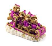 Handmade медведи рождества в санях в фиолете и куртках и шляпах золота на изолированном снеге Стоковая Фотография RF