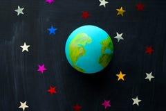 handmade модель планеты земли и sequins в форме звезд на концепции доски, космоса и астрономии стоковое изображение