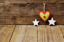 Handmade от сердца войлока, белых звезд на деревянной предпосылке с Стоковое Фото