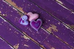 Handmade сердца игрушки войлока ткани на старом фиолетовом деревянном поле Стоковое Изображение RF