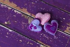 Handmade сердца игрушки войлока ткани на старом фиолетовом деревянном поле Стоковые Фотографии RF