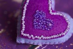 Handmade сердца игрушки войлока ткани на старом фиолетовом деревянном поле Стоковые Изображения RF