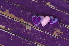Handmade сердца игрушки войлока ткани на старом фиолетовом деревянном поле Стоковая Фотография RF