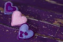 Handmade сердца игрушки войлока ткани на старом фиолетовом деревянном поле Стоковое фото RF