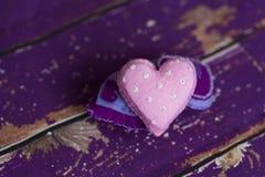 Handmade сердца игрушки войлока ткани на старом фиолетовом деревянном поле Стоковое Фото