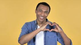 Handmade сердце молодым африканским человеком, желтой предпосылкой