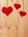 Handmade сердца вися на линии против стены древесин-зерна Стоковые Изображения RF