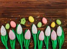 Handmade тюльпаны и пасхальные яйца на деревянной предпосылке Стоковое фото RF