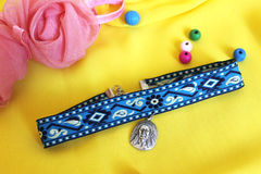 Handmade accessories blue choker with a silver pendant on a yellow background. Handmade choker blue choker with a silver pendant on a yellow background with pink stock photos