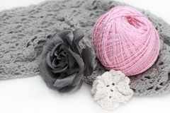 Handmade accessories. Gray crocheted material and pink clew, flower Stock Photography