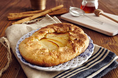 Handmade apple pie. On a dish over a napkin in a country style, cinnamon and hony in the background Royalty Free Stock Images