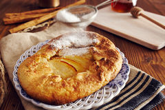 Handmade apple pie. On a dish over a napkin in a country style, cinnamon and hony in the background Royalty Free Stock Photos