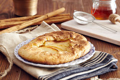Handmade apple pie. On a dish over a napkin in a country style, cinnamon and hony in the background Stock Image