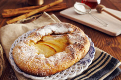 Handmade apple pie. On a dish over a napkin in a country style, cinnamon and hony in the background Royalty Free Stock Photography