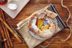 Handmade apple pie. On a dish over a napkin in a country style, cinnamon and hony in the background Stock Photography